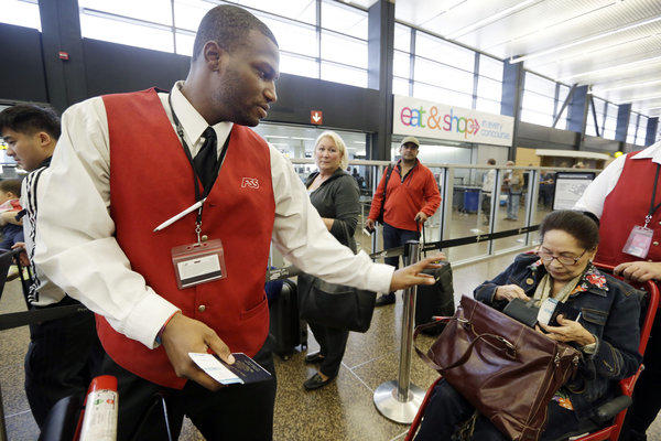 Wheelchair attendant Erick Conley, left, assists an elderly passenger heading overseas at Seattle-Tacoma International Airport in SeaTac, Wash. Voters will decide on whether to raise the city's minimum wage to $15 an hour.