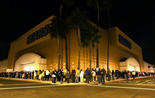 Sears plans to welcome patrons at 8 p.m. on Thanksgiving and run special deals until 1 p.m. the next day. Above, hundreds of shoppers line up at Sears' South Coast Plaza store for the day after Thanksgiving bargains minutes before the 4 a.m. opening in 2009.