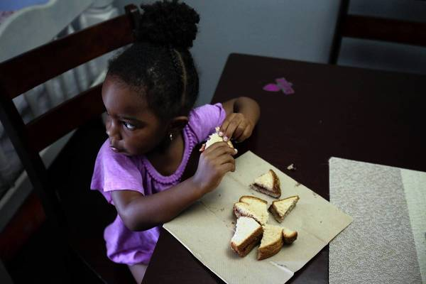 Two-year-old Ausara Mudahy eats dinner, a peanut butter and jelly sandwich on wheat bead, in Culver City last week. Her mother, who works two jobs, receives food-stamp benefits.