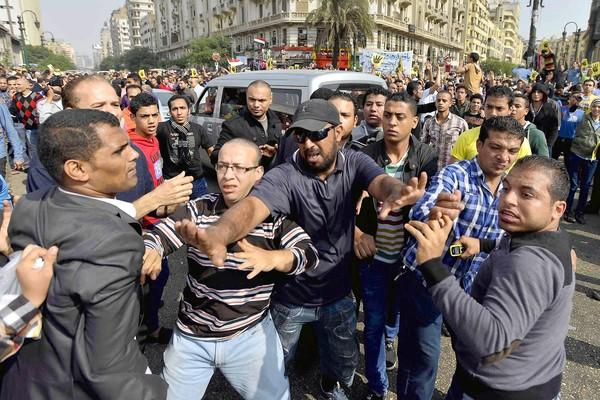 An Egyptian intervenes as government supporters, left, clash with backers of deposed Islamist President Mohamed Morsi in Cairo, where Morsi's trial got underway.