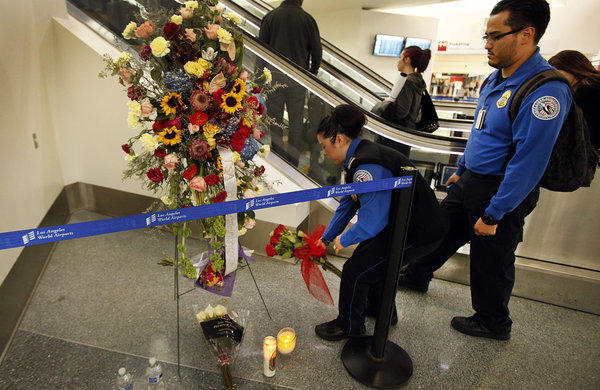 Transportation Security Administration agents leave flowers and say a prayer at a memorial at LAX.