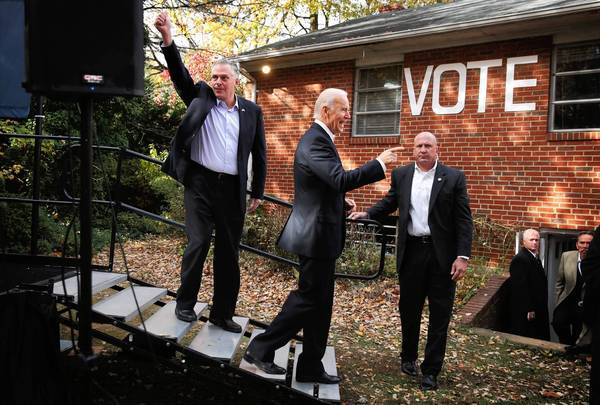 Former Democratic Party Chairman Terry McAuliffe, left, leaves a campaign rally in Annandale, Va., with Vice President Joe Biden on Monday. McAuliffe is expected to win the governor's seat in Virginia on Tuesday.