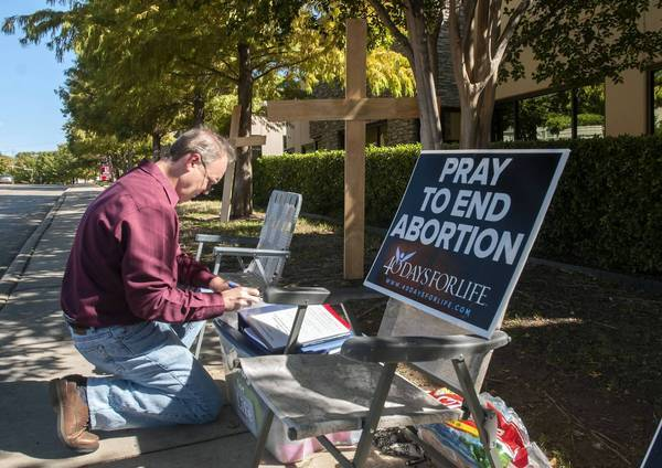 A man adds his name to a list of people holding a vigil outside an abortion clinic in Dallas.