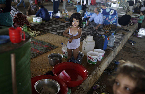 Ruwa Bazara takes a bath at a Syrian border crossing as her family waits in hope of entering a refugee camp in Turkey.