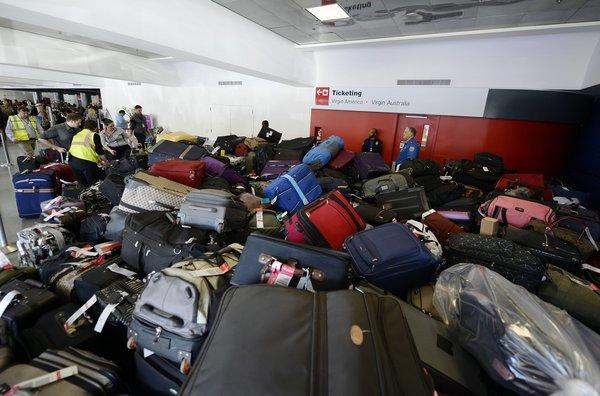 Luggage waits to be screened in Terminal 3 a day after the LAX shooting.