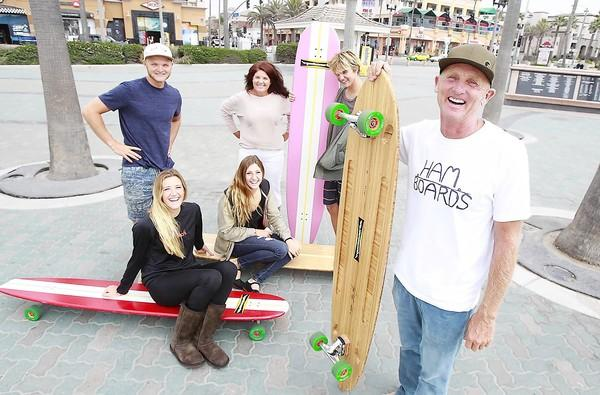 "Pete Hamborg, right, stands with the Hamboards crew including Moses Hamborg, Kendra Koelsch, in black, Sawyer Koelsch, wife Kathy Hamborg, and Anders Hamborg at the base of the Huntington Beach Pier where they ride. Hamboards were featured on a recent episode of ""Shark Tank."""