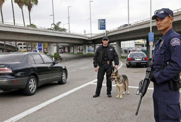 Los Angeles Airport officer Daniel Keene, left, police dog Axa and officer Fritz Corros stand at a checkpoint outside Los Angeles International Airport.