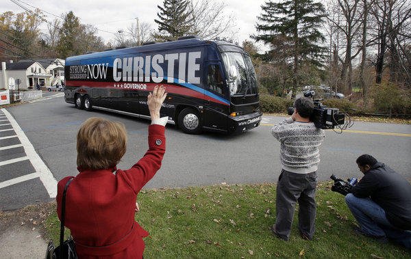 Judy Feldman, 65, waves as a bus carrying New Jersey Gov. Chris Christie passes after he voted in Mendham Township, N.J. The Republican governor is running against Democrat Barbara Buono.