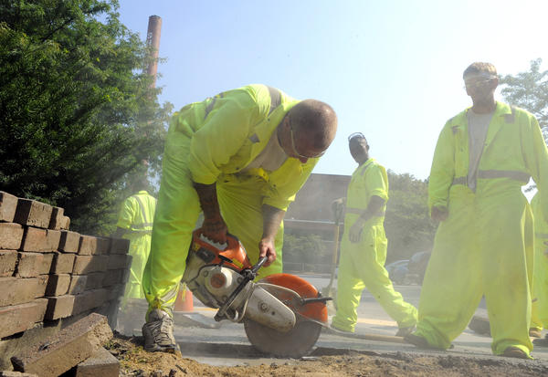 Workers help to fix curbs in downtown Westminster, a project helped along by inmate labor.