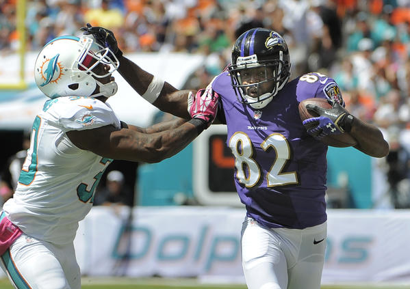 Ravens wide receiver Torrey Smith holds off Dolphins' Chris Clemons in a game on Oct. 6.