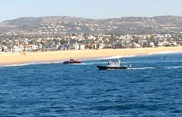 A frame grab from cell phone video shows the scene where a man jumped from a helicopter into the water south of Balboa Pier.