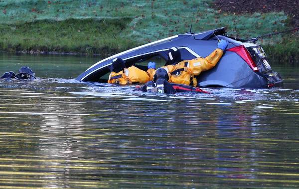 Rescue personnel pull Henry Laseke's car from a pond next to his Arlington Heights home July 25. He had driven the car into the water and drowned.