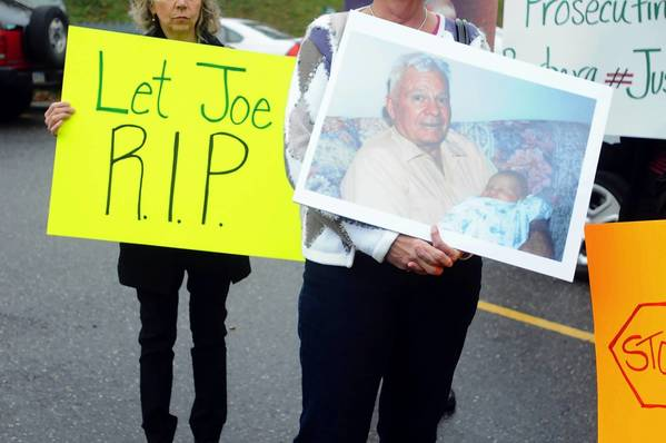 Friends and family hold signs and pictures before a hearing for Barbara J. Mancini in Pottsville, Pa. She is charged with assisted suicide in the death of her father, Joe Yourshaw, whose photo is being held at right.