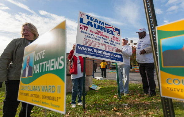 Incumbent City Council members Donna Crary (left), Edward Ricks and Frederick Smalls help post a Team Laurel sign outside the Robert J. DiPietro Community Center Tuesday morning. All five incumbent Council member won re-election.