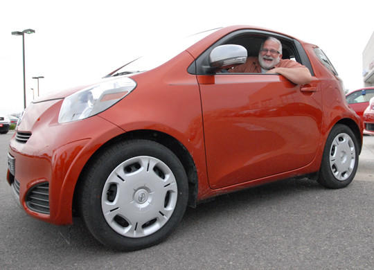 Jim Walker, the artistic and managing director of Aberdeen Community Theatre, sits inside the 2013 Scion iQ which is being raffled off by ACT.