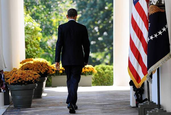 President Obama walks to the Oval Office after speaking about the Affordable Care Act in the White House Rose Garden.