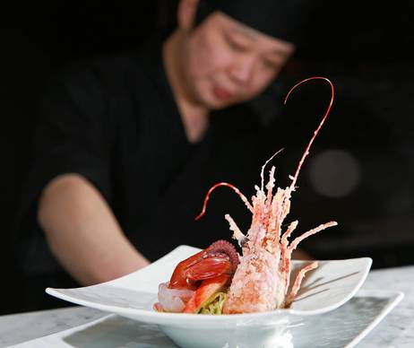 Chef Jinwoo Han prepares a dish after completing a portion of a 5 course tasting menu that includes Kani, Tako, and Ama ebi (king crab, octopus, sweet shrimp) at Masaki.