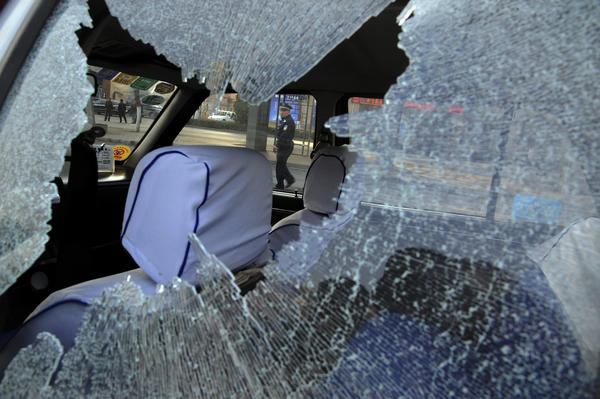 A Chinese police officer is framed by the shattered window of a vehicle damaged in a series of explosions at the Communist Party headquarters in the provincial city of Taiyuan.