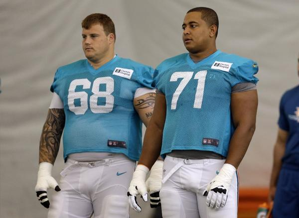 In this July 24, 2013 file photo, Miami Dolphins guard Richie Incognito (68) and tackle Jonathan Martin (71) stand on the field during practice.