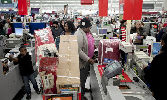 Shoppers wait in a check out line at Kmart during the Black Friday sales last November in Braintree, Mass.