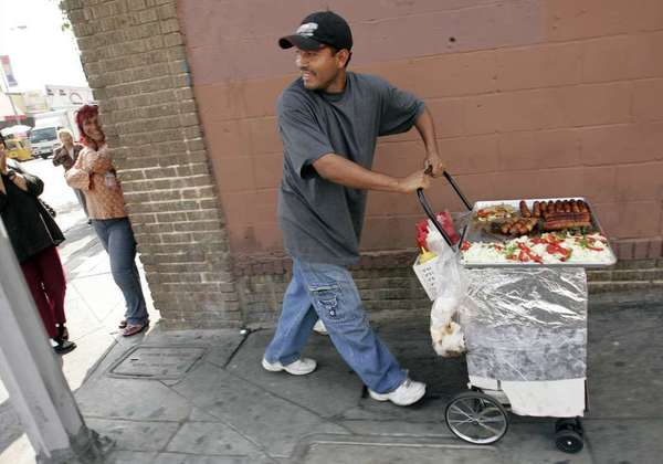 Two L.A. City Council members are calling for a study of how the city can legalize street vending. Above, a file photo of a hot-dog vendor in downtown L.A.