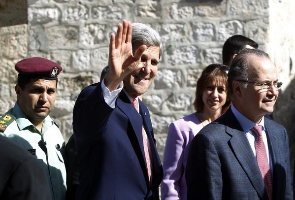 Secretary of State John F. Kerry waves during a visit to the West Bank.