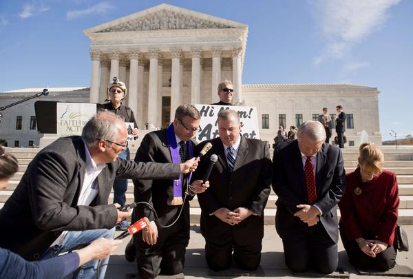 Religious activists pray outside the Supreme Court following oral arguments in the case of Town of Greece vs. Galloway.
