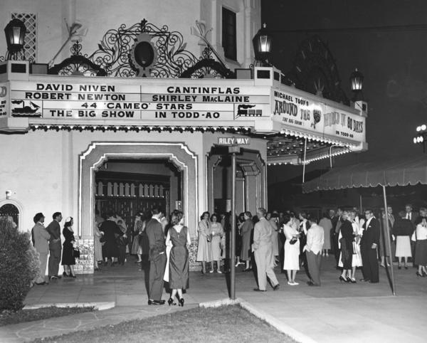 In 1956, Glendale photographer Glenn B. Ward was hired to document the opening of the Cinerama at Carthay Circle. His wife, Betty, and two daughters, Sharon and Peggy, were unpaid extras. Betty (in light coat and dark shoes), Sharon (in light dress and light shoes) and Peggy (dark shoes, in the shadow of the pole) all stand to the left of the Riley Way street sign. (Courtesy of Sharon Ward Thompson)