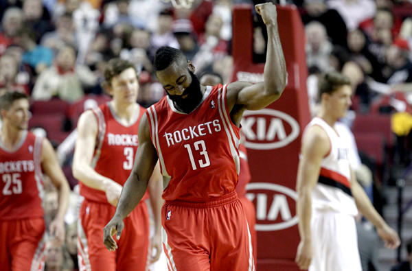 Rockets guard James Harden celebrates after making a three-point shot against the Trail Blazers on Tuesday.