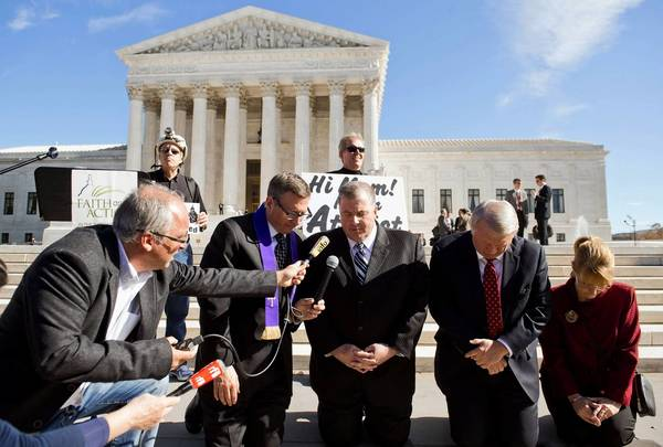 Religious activists pray outside the Supreme Court after oral arguments in the case of Town of Greece vs. Galloway.