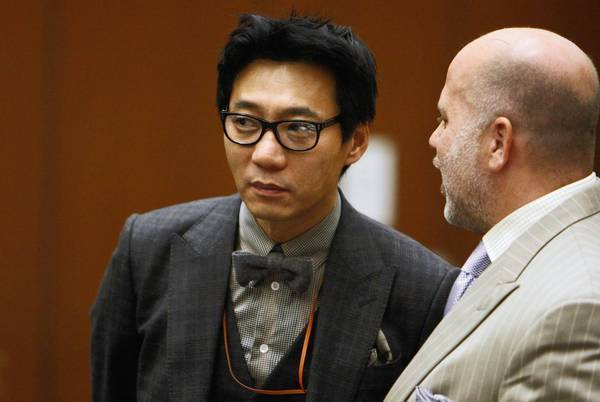 Young Lee, left, one of the founders of the Pinkberry yogurt empire, with his attorney Philip Kent Cohen, right, during his arraignment in 2012. The defense argues that another man beat the victim with a tire iron.