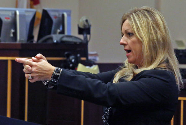 Prosecutor Linda Drane Burdick strikes a pose showing how defendant Jason Rodriguez held his gun as he went on a 2009 shooting spree at an engineering firm Reynolds, Smith & Hills.