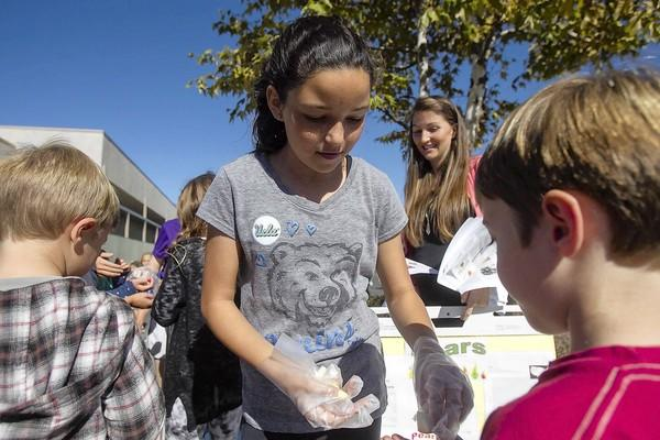 Leah West, 10, a fifth-grade student at Top of the World Elementary School, hands out Comice pears during a taste test at recess on Tuesday.