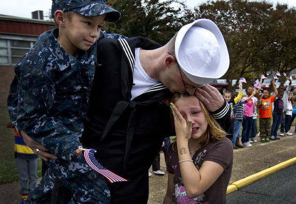 Petty Officer 1st class Adam McPheron picks up Riley Bolt 8 yrs. a 2nd grader while caring for a crying and upset Savannah Bolt 10. Petty Officer 1st class Adam McPheron a sailor stationed on the USS Kearsarge for the past eight months returned and surprise his three children at Barron Fundamental Elementary who had all 400 students out with flags to greet him home.