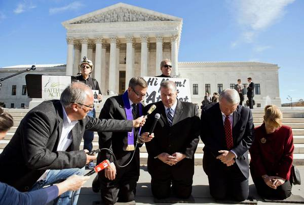 Religious activists pray following oral arguments in the case of Town of Greece v. Galloway dealing with prayer in government, outside the Supreme Court on Wednesday. The case deals with whether holding a prayer prior to the monthly public meetings in the New York town of Greece violates the Constitution by endorsing a single faith.