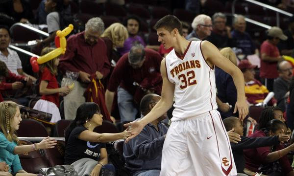 USC's Nikola Jovanovic high-fives fans sitting courtside during a team scrimmage on Oct. 27 at Galen Center.