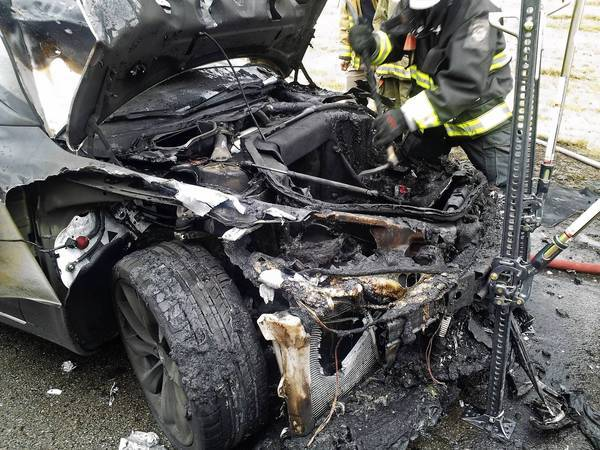 Emergency crews examine a Tesla Model S hatchback that caught fire after a crash Wednesday in Smyrna, Tenn. Tesla plans to investigate the blaze.