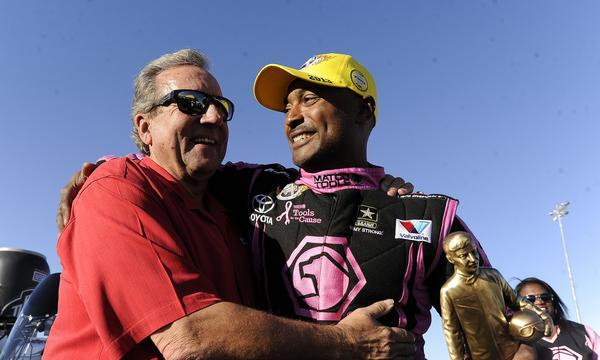 NHRA top fuel dragster driver Antron Brown, right, is congratulated by team owner Don Schumacher after winning an NHRA event in Las Vegas on Oct. 27. Brown has let his scary crash at the Winternationals hasn't slowed him down at Pomona this week.