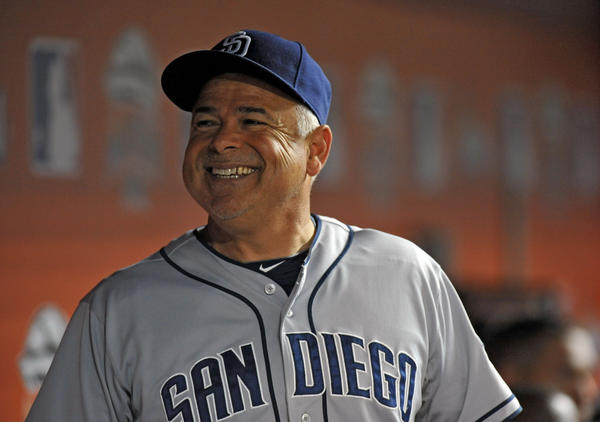 Rick Renteria smiles in the Padres dugout during a game.