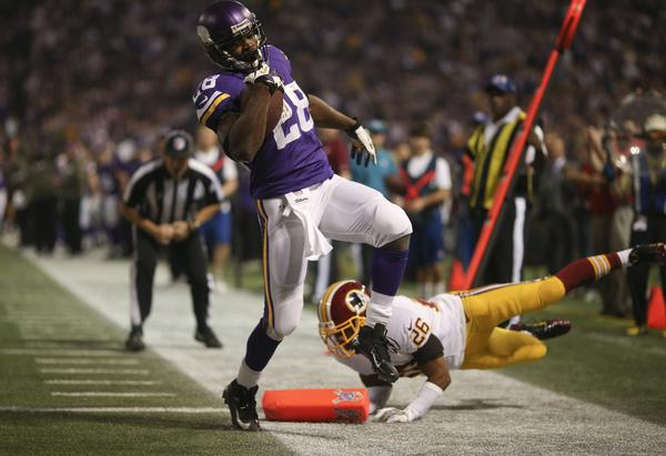Vikings running back Adrian Peterson breaks the tackle of the Redskins' Josh Wilson at the goal line for an 18-yard touchdown run in the first quarter.