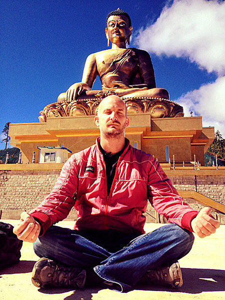 In Thimphu, Bhutan, Leon Logothetis sits in front of a statue of Buddha. Bhutanese believe in the Gross National Happiness Index.