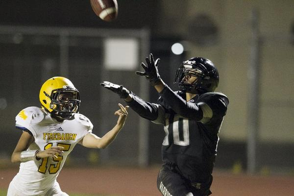 Brethren Christian's Guy Demazelier catches a touchdown pass over Firebaugh's Thomas Marquez on Thursday.
