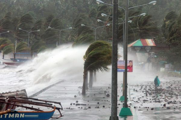 A resident (R) walks past high waves pounding the sea wall amidst strong winds as Typhoon Haiyan hit the city of Legaspi, Albay province, south of Manila on November 8, 2013. One of the most intense typhoons on record whipped the Philippines on November 8, killing three people and terrifying millions as monster winds tore roofs off buildings and giant waves washed away flimsy homes.