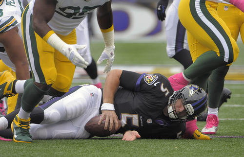 Ravens quarterback Joe Flacco stays on the ground after being sacked by the Green Bay Packers in the first quarter.