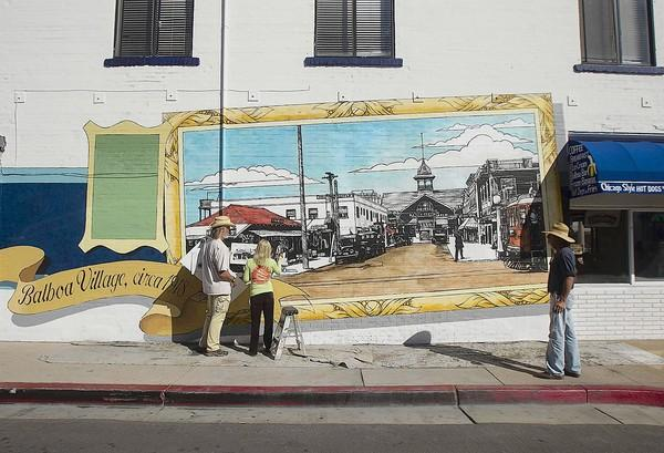 West Los Angeles artist Art Mortimer, left, directs Jule Gainey as she paints a mural of Balboa Village history while Norm White, right, looks on Wednesday.