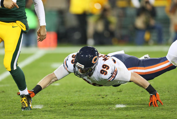 Shea McClellin of the Chicago Bears reaches for the ankle of Green Bay Packers quarterback Seneca Wallace Monday night.