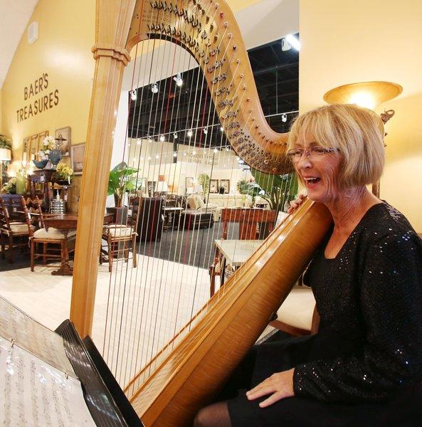 Petra Trevino plays the harp during the grand opening of Baer's Furniture in West Melbourne on Thursday, November 7, 2013. (Stephen M. Dowell/Orlando Sentinel)