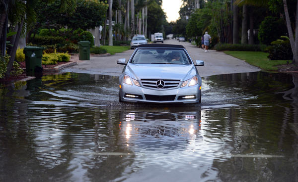 A driver on Las Olas Isles is forced through a puddle at Coral Way, Wednesday, Oct. 16, 2013, in a scene typical of the area at high tide.(c)2013