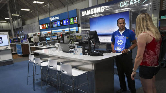 Best Buy employee Phillip Stewart helps Karen Karpenko in the Richfield, Minn., store in July.