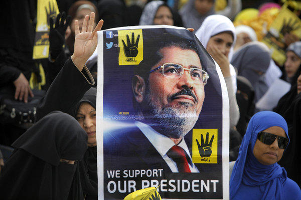 Supporters of Egypt's ousted president Mohamed Morsi carry a picture of him Friday during a protest in Cairo.